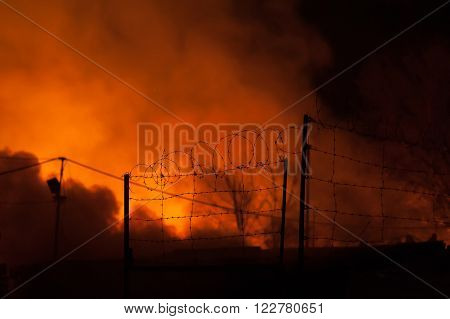Firefighters battles storage fire. focus on Fences with barbed wire. Night Scene with a fiery glow in the background.