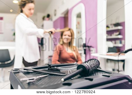 Hair stylist straightening hair to her customer in a modern hairdresser salon closeup on brushes and scissors