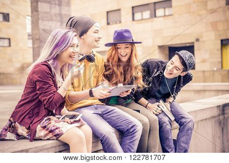 Multiracial group of best friends laughing and having fun outdoors - Multiethnic young teenagers looking down at computer tablet