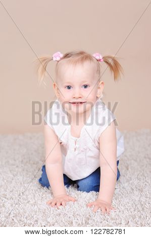Smiling baby girl 2-3 year old sitting on floor looking at camera. Posing in room.