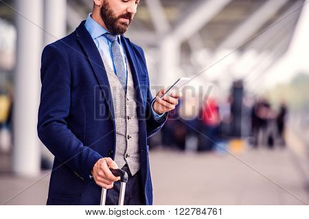 Hipster businessman in suit with smart phone, waiting at the airport, sunny day