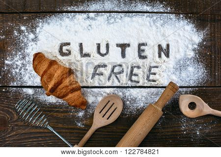 Top view studio shot of gluten-free word with flour and croissant on wooden table
