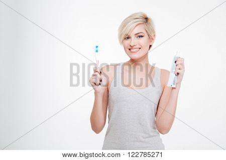 Portrait of a happy blonde woman holding toothbrush and toothpaste isolated on a white background