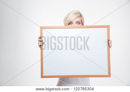 Blonde woman peeking from blank board isolated on a white background