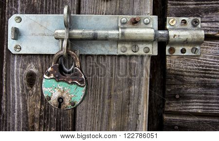 Rusty padlock and latch on old wooden door