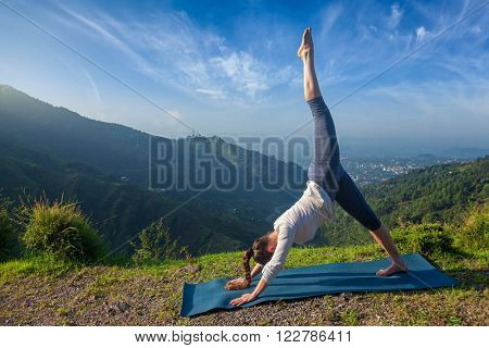 Young sporty fit woman doing yoga asana Adho mukha svanasana - downward facing dog variation outdoors in Himalayas in the morning