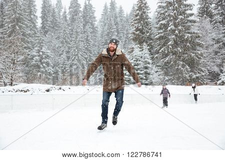 Handsome man ice skating outdoors with snow on background