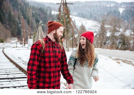 Laughing couple traveling together on railway with forest and mountain on background