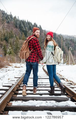 Smiling young couple walking on railway with forest on background