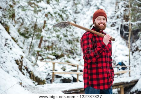 Young man holding shovel outdoors with snow on background