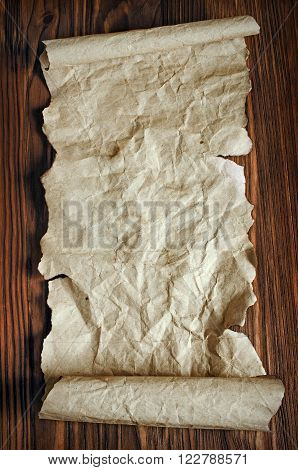The ancient parchment or unrolled scroll on a wooden background