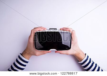 Hands of man holding virtual reality goggles. Flat lay. Studio shot on gray background.