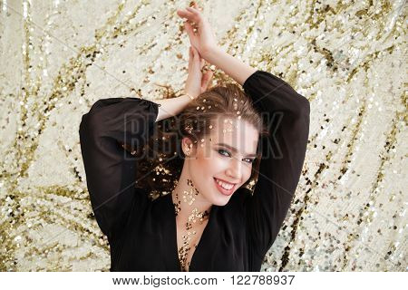 Top view of happy beautiful young woman with sequins on her face lying and smiling over sparkling background