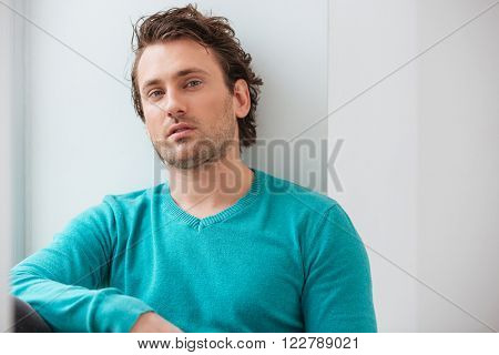 Portrait of handsome relaxed young man in blue jumper over white background