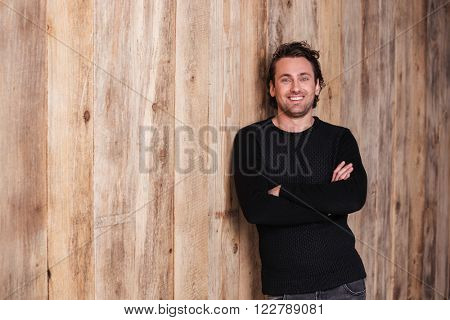 Smiling attractive young man in black jumper standing with hands folded over wooden background