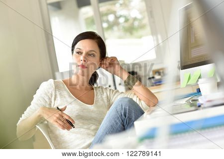 Woman in office with a thoughtful look