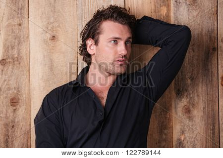 Portrait of handsome curly young man in black shirt with hand behind head looking away over wooden background