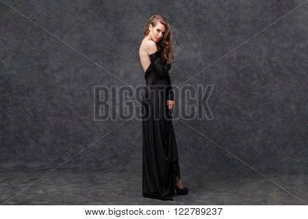 Full length portrait of tempting lovely young woman in long black dress with open back over grey background