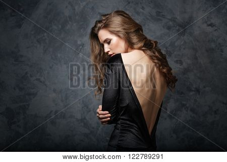 Beautiful young woman in black dress with open back standing and looking down over grey background