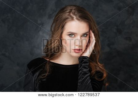 Beauty portrait of sensual young woman touching sking on her face over grey background