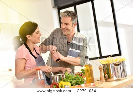 Middle-aged couple having fun cooking together