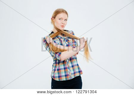 Funny woman holding her ponytails isolated on a white background