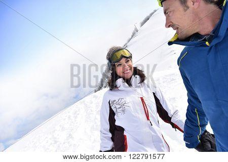 Couple having fun running down ski slope