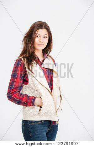 Portrait of beautiful young woman in checkered shirt and waistcoat standing with hands in pockets