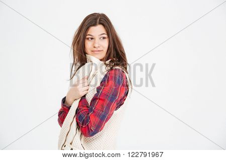 Attractive young woman in plaid shirt and waistcoat posing over white background