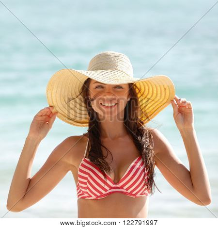 Portrait of a beautiful young woman in sunhat on beach