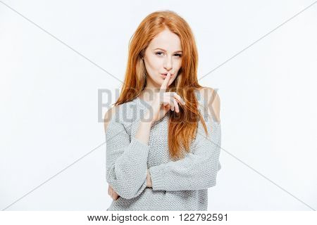 Redhead woman showing finger over lips isolated on a white background