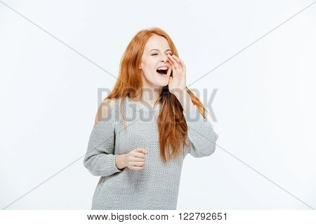 Redhead woman calling somebody isolated on a white background