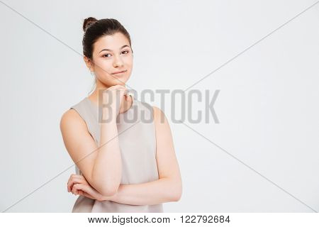 Portrait of smiling attractive young business woman with hands folded over white background