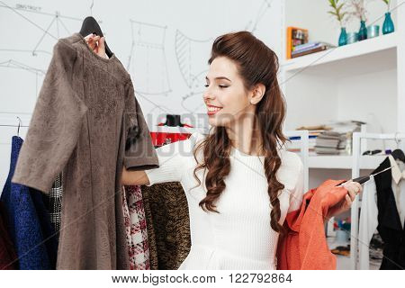 Smiling woman choosing dress in the shop