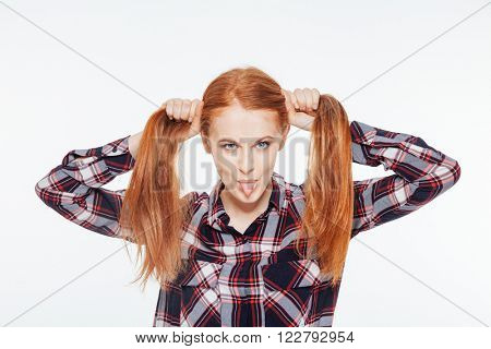 Redhead woman holding her ponytails and showing her tongue isolated on a white background