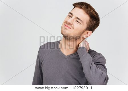 Sad unhappy young man in grey pullover suffering from neck pain over white background