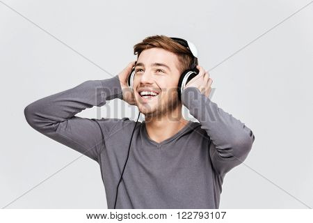 Cheerful attractive young man in headphones listening to music over white background
