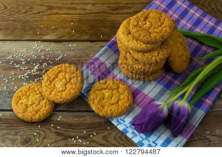 Homemade sesame cookies and two purple tulips on the linen napkin. Breakfast cookie. Dessert cookies. Cookies. Cookie. Dessert. Breakfast.