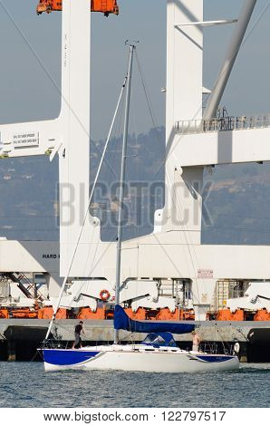 Alameda, CA - March 9, 2015: Oakland Container Shipyard, San Francisco Bay prvate boat cruising among the ships in the harbor