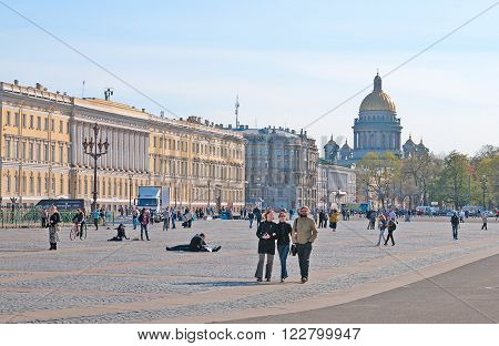 Saint Petersburg, Russia - May 14, 2011: People walk on The Palace Square. On the background is The St Isaac's Cathedral. The Palace Square and St Isaac's Cathedral located in historic center of Saint Petersburg.