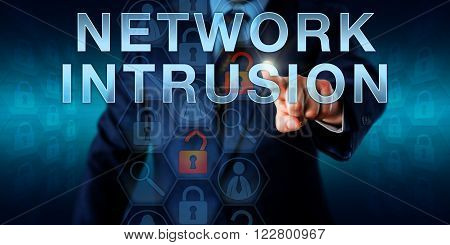 Cybercriminal intruder touching NETWORK INTRUSION on a virtual screen. Information technology metaphor and security concept for harmful attacks and malicious violations within a network or system.