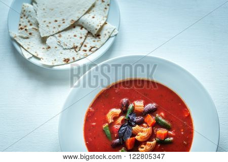 Portion Of Minestrone Soup WIth Fresh Basil And Bread
