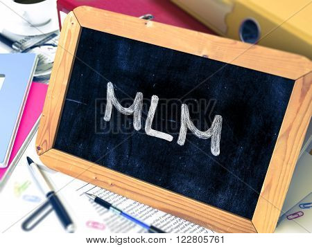 Handwritten MLM - Multi Level Marketing - on a Chalkboard. Composition with Chalkboard and Ring Binders, Office Supplies, Reports on Blurred Background. Toned Image. 3D Render.