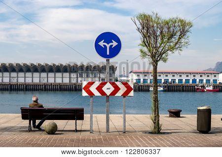 SANTANDER, SPAIN - APRIL 2015: older man back sitting on a bench looking at the fishing port.