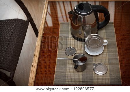 Morning coffee served in vietnam coffee filter on rattan table with two rattan chairs natural light photo closeup horizontal view