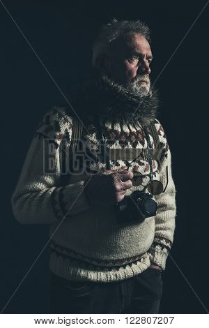Vintage old mountaineer with knitted sweater fur collar and SLR camera.