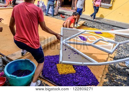 Antigua Guatemala - March 20 2016: Locals decorate Palm Sunday carpet using stencils & dyed sawdust for procession in colonial town with most famous Holy Week celebrations in Latin America.