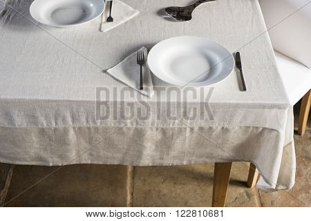 Sets Of Dinnerware Arranged On White Linen-covered Table