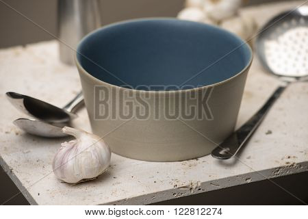 Empty Beige Flat Bottom Soup Bowl With Spoons And Garlic