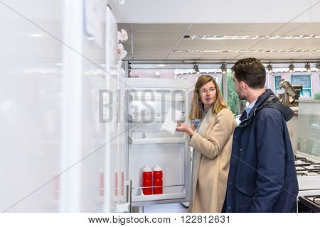 Young woman holding ice tray while talking with man at refrigerator section in hypermarket
